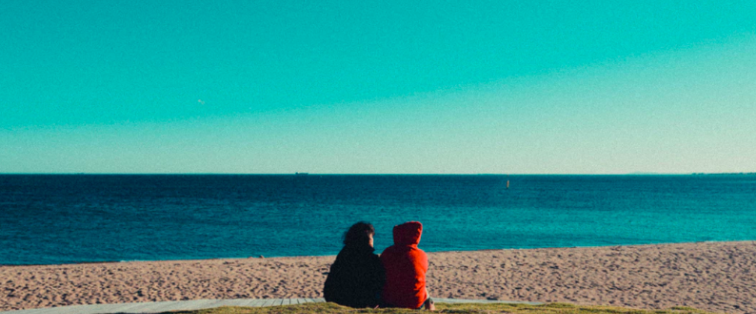 Two teenagers sitting together at the beach