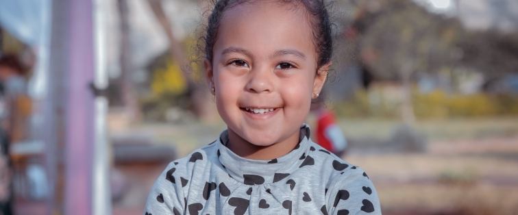 young girl smiling outside at the park