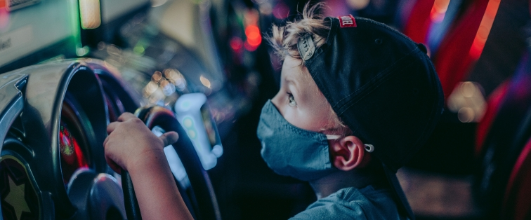 child wearing a mask amid COVID-19 pandemic at the arcade