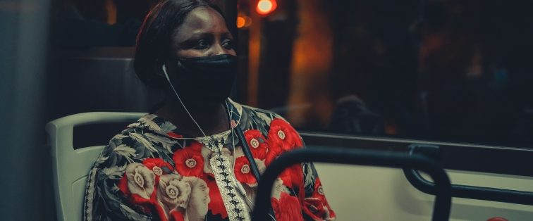 woman sitting on public transit listening to music while wearing a mask amid COVID-19
