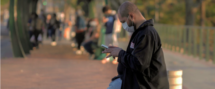 man with mask in city texting on his cell phone