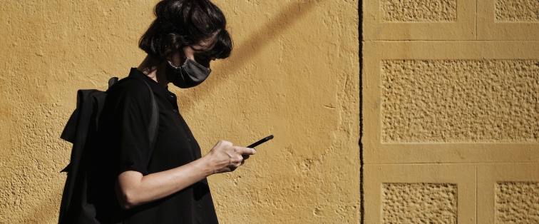 woman walking with mask and headphones while texting on her cell phone