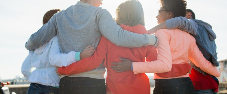 A group of multiracial adolescent friends hugging and looking at each other as they face away from the camera.