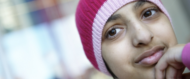 Profile of an adolescent female with a pink hat on and her hand under her chin