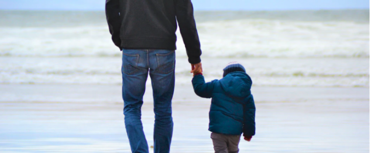 father and son holding hands walking on the beach