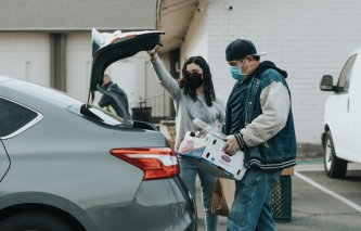 two individuals unpacking a car wearing a mask amid the COVID-19 pandemic