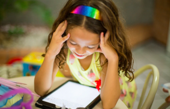 young girl using a tablet smiling