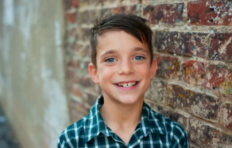 boy smiling at the camera standing in front of a wall