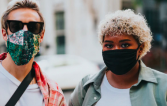 man and woman wearing a mask looking at the camera