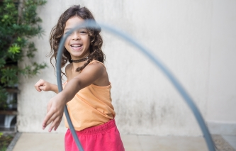 young girl smiling and playing with hoola hoop